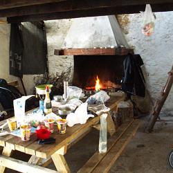 Pièce à vivre, table bancs, cheminée une fenêtre.